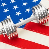 Metal dumbbell over US flag as symbol of healthy nation - studio shot — Stock Photo