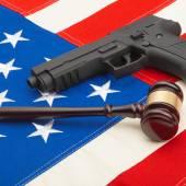 Neat judge gavel and gun over USA flag - studio shoot — Stock Photo