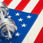 Metal dumbbell over US flag — Stock fotografie