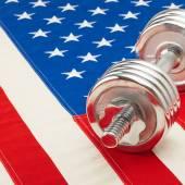 Metal dumbbell over US flag as symbol of bodybuilding - studio shot — Stock fotografie