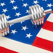 Metal dumbbell over US flag as symbol of bodybuilding — 图库照片