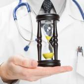 Doctor holdling in his hand a hourglass - medical aid concept — Stock Photo