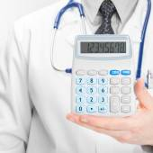Doctor holdling in his hand calculator - medical aid concept — Stock Photo