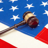 Wooden judge gavel over US flag - court judgment concept — Stockfoto