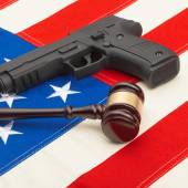 Wooden judge gavel and gun over USA flag - self-defense law concept — Stock Photo