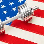 Metal dumbbells over USA flag as symbol of healthy nation - healthy lifestyle concept — Stock Photo