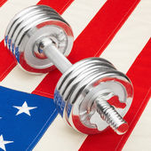 Metal dumbbells over US flag as symbol of healthy nation - healthy lifestyle concept — Stock Photo