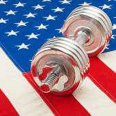 Metal dumbbell over US flag as symbol of healthy life style - healthy lifestyle concept — Stock Photo