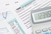 Calculator over US 1040 Tax Form — Stock Photo