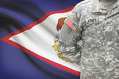 American soldier with flag on background - American Samoa — Stock Photo