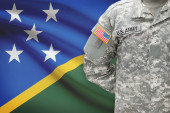 American soldier with flag on background - Solomon Islands — Stock Photo