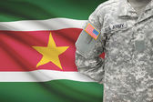 American soldier with flag on background - Surinam — Stock Photo