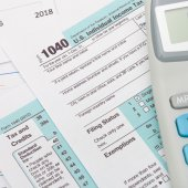 US 1040 Tax Form and calculator over it - studio shot — Stock Photo