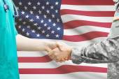 Soldier and doctor shaking hands. Flag on background - United States — 图库照片