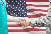 Soldier and doctor shaking hands. Flag on background - United States — Fotografia Stock