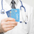 Medical doctor holding two credit cards in his hand - closeup shot — Stock Photo #64996597