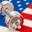 Silver color dumbbell over US flag as symbol of healthy life style — Stock fotografie #64996709