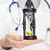 Medical doctor and hourglass - heath care concept — Stock Photo