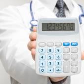 Medical doctor holding calculator - closeup shot — Zdjęcie stockowe