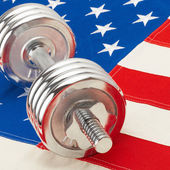 Silver color dumbbell over US flag as symbol of healthy life style — Stock Photo