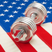 Shiny dumbbell over US flag as symbol of healthy life style - studio shot — Stock Photo