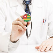Doctor holding stethoscope with flag series - Togo — Stock Photo