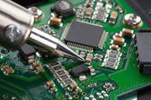 Close up studio shot of soldering iron and microcircuit — Stock Photo