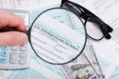 USA 1040 Tax Form 1040 with magnifying glass, glasses, dollars and calculator over it — Stock Photo