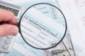 Tax Form with magnifying glass calculator and dollars — Stock Photo