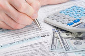 Taxpayer filling out USA 1040 Tax Form - studio shot — Stock Photo