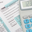 US 1040 Tax Form and calculator over it - studio shot — Stock Photo #67538777