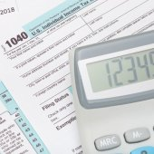 Calculator over US 1040 Tax Form - studio shot — Stock Photo