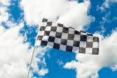 Checkered flag waving in the wind with clouds on background - outdoors shoot — Stock Photo