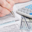 Taxpayer filling out USA 1040 Tax Form - studio shot — Stock Photo #68248297