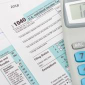US 1040 Tax Form and calculator over it — Stock Photo