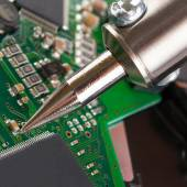 Soldering iron and microcircuit - closeup studio shot — Stock Photo