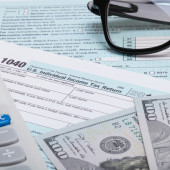 US 1040 Tax Form, calculator, glasses and dollars - studio shot — Stock Photo