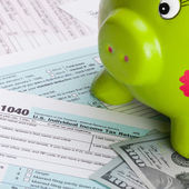Hundred dollars banknote and piggy bank over US tax form — Stock Photo