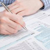 Taxpayer filling out 1040 Tax Form - studio shot — Stock Photo