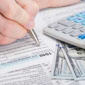 Taxpayer filling out USA 1040 Tax Form - studio shot — Stockfoto