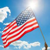 American flag waving in blue sky with sun behind it — Stock Photo