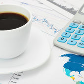 Coffee cup and calculator over world map and some financial char — Stock Photo