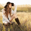 Beautiful young lady model sitting in field at sunrise — Stock Photo #69131801