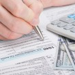 Taxpayer filling out USA 1040 Tax Form - close up studio shot — Stock Photo #69537441