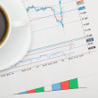 Coffee cup and financial charts - close up shot — Stock Photo #69537659