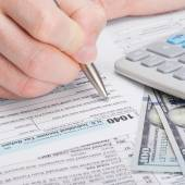 Taxpayer filling out USA 1040 Tax Form - close up studio shot — Foto de Stock