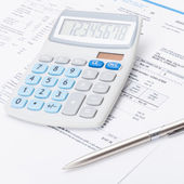 Neat calculator with silver pen and utility bill under it - close up shot — Stock Photo