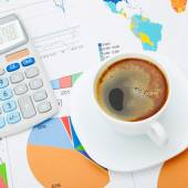 Coffee cup and calculator over financial documents - close up studio shot — Stock Photo