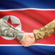 Men in uniform shaking hands with flag on background - North Korea — Stock Photo #71988499
