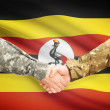 Men in uniform shaking hands with flag on background - Uganda — Stock Photo #71988781